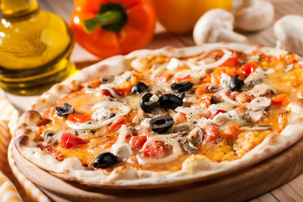 hot flatbread pizza with cooked chicken, olives, onions, marinara, and mozzarella cheese