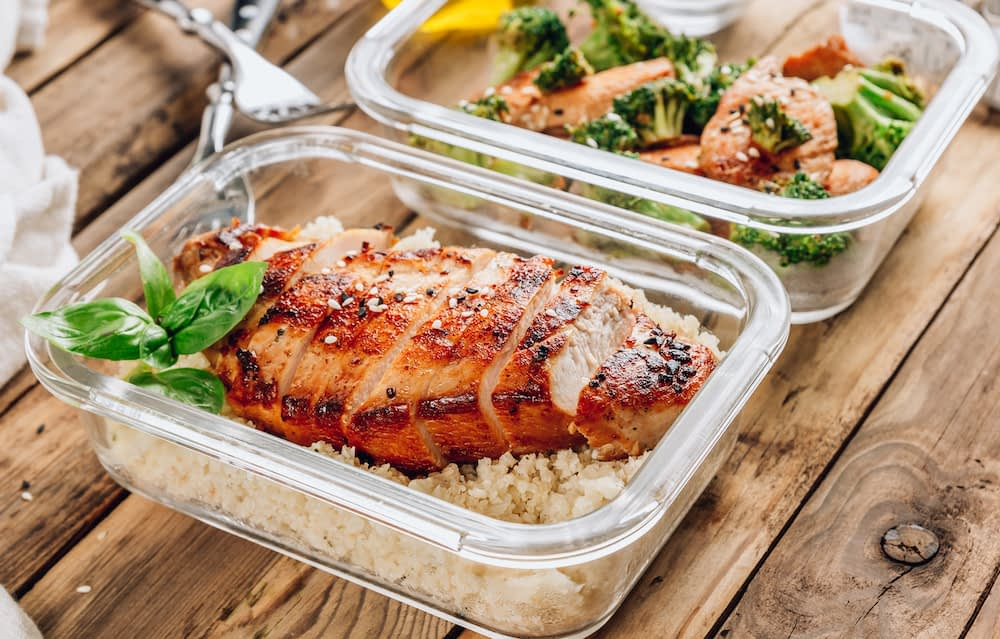 glass container with a grilled chicken breast on top of a bed of brown rice