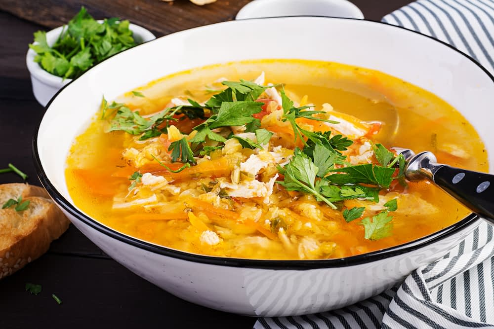hot homemade lentil soup with chicken, vegetables, and herbs