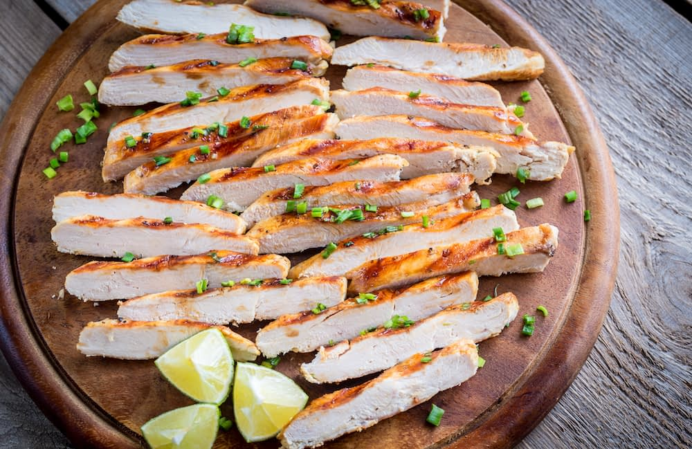 Leftover chicken sliced on a cutting board with lime and cilantro