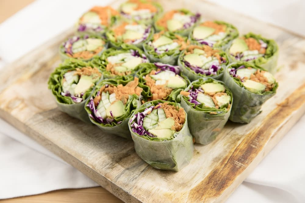 Spring sliced summer rolls with chicken, cabbage and carrot on a wooden cutting board