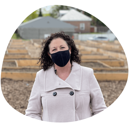 CEO of capital roots amy klein, standing in front o a new community garden wearing a black medical mask and a white coat.