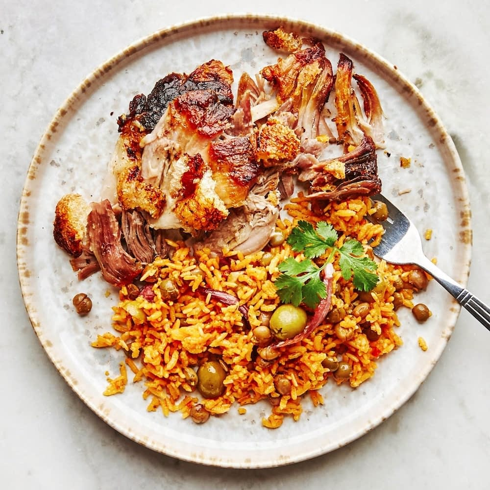 Plate with yellow rice and pigeon peas served with pork - arroz con gandules