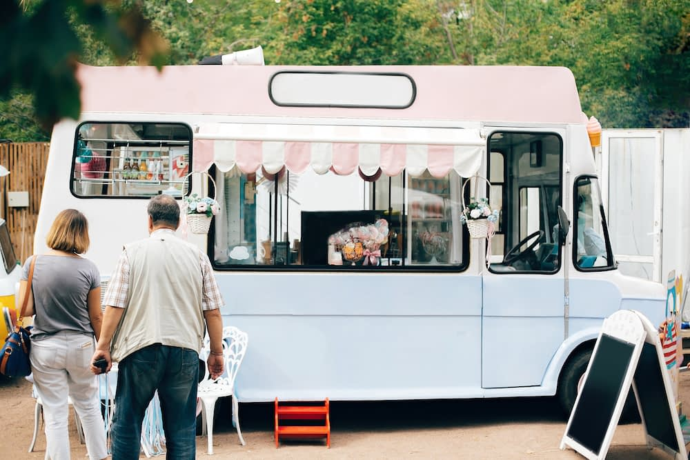 Vintage colorful food truck peddling various candies to older couple