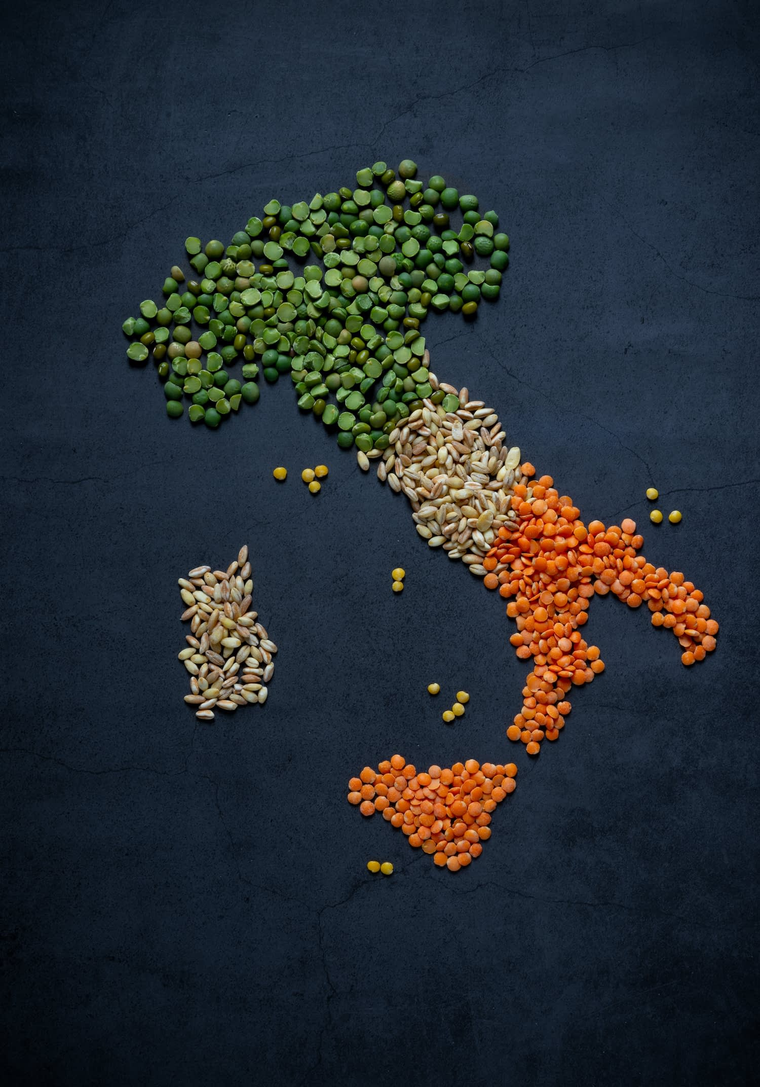 Image of dry goods, lentils, peas, arranged in the shape of Italy to show history of global trade.