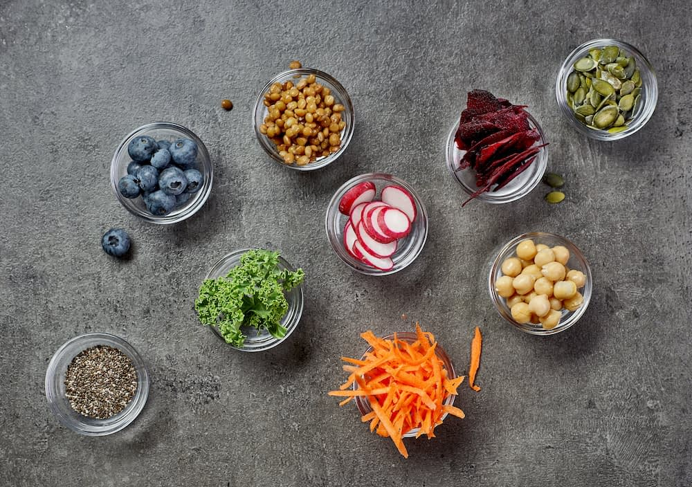 healthy food ingredients in small bowls. Food like berries, kale, lentils, chia seeds, radish, and carrots