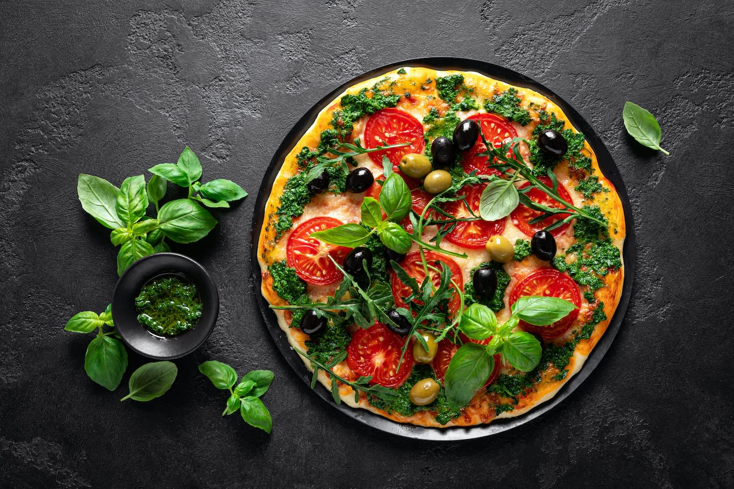 Simple, traditional thin crust Italian pizza with basil, tomato, pesto and olives