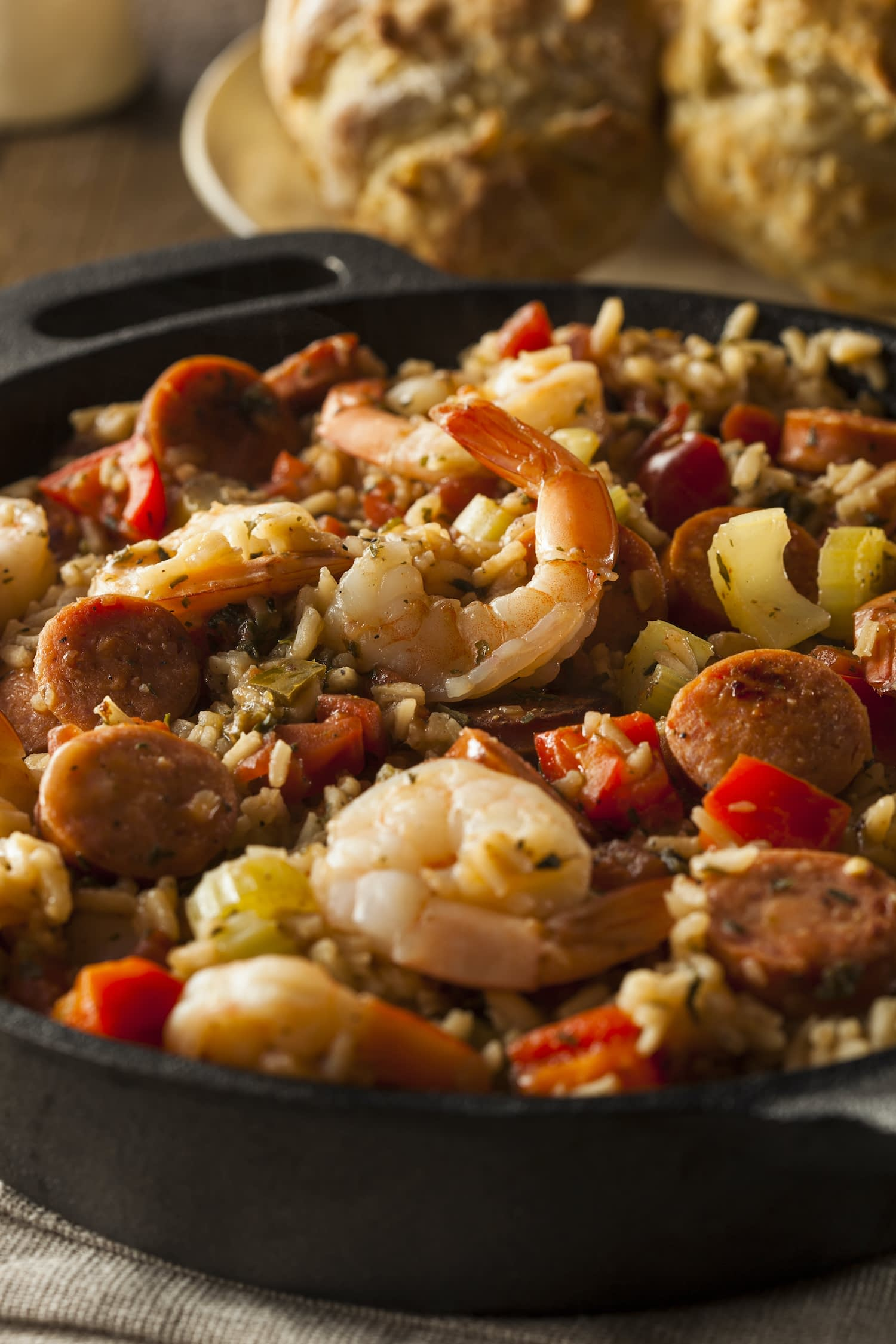 Spicy New Orleans cajun jambalaya with shrimp, peppers and celery in cast-iron skillet.