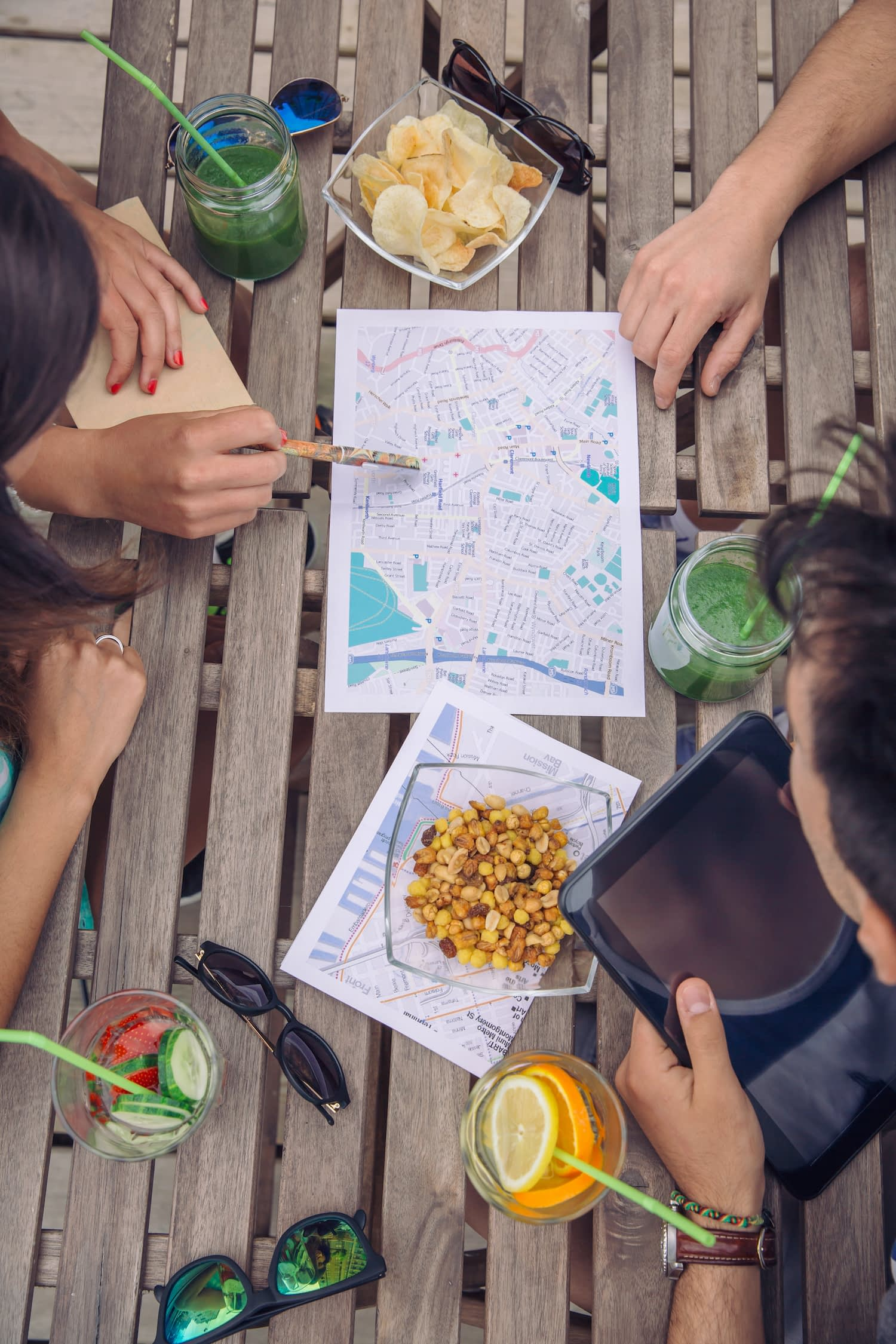 Young tourists enjoying variety of snacks while studying map, deciding where to go next.