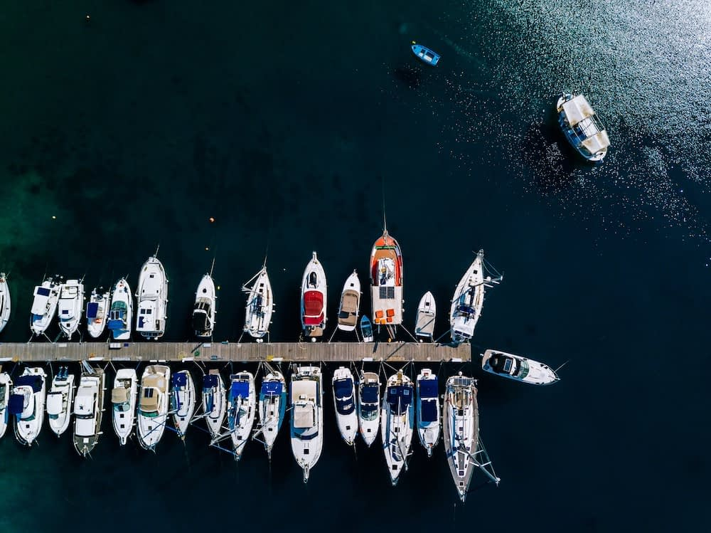 aerial view of a marina lot of boats in a port of the ocean contributing to overfishing