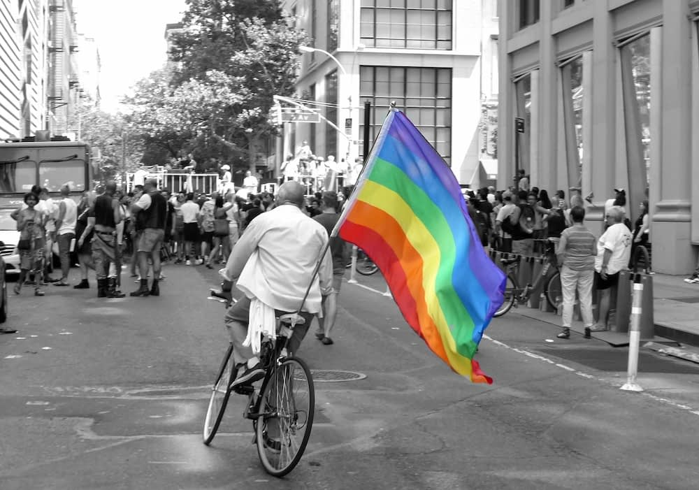 A black and white photo of a man bicycling through a city street. Attached to the back of the bike is  Pride flag, which is in color.