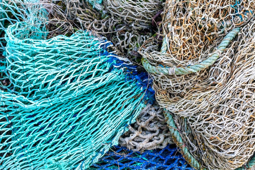 a background of fishing nets of different colors like white, aqua, and dark blue