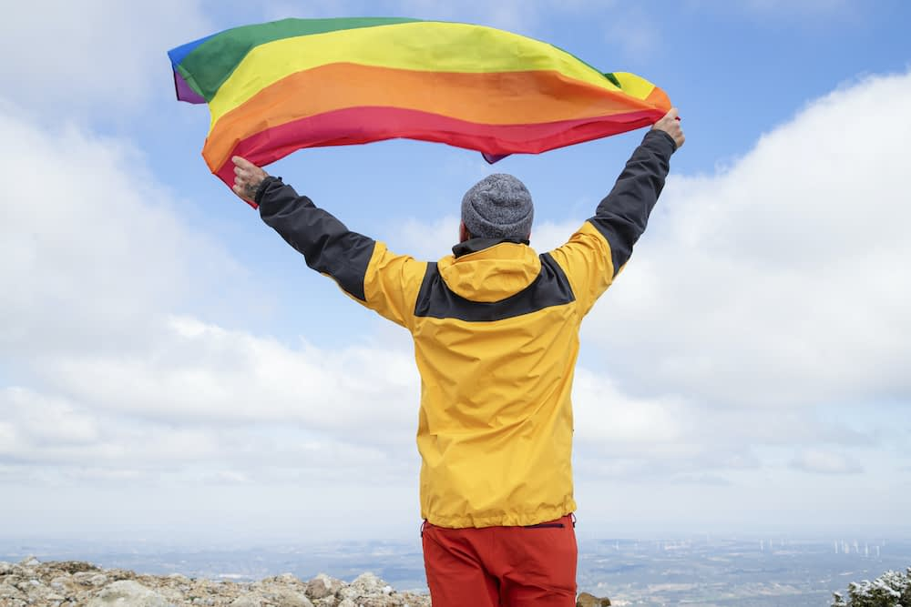 A hiker waving a Pride flag at the top of a mountain.